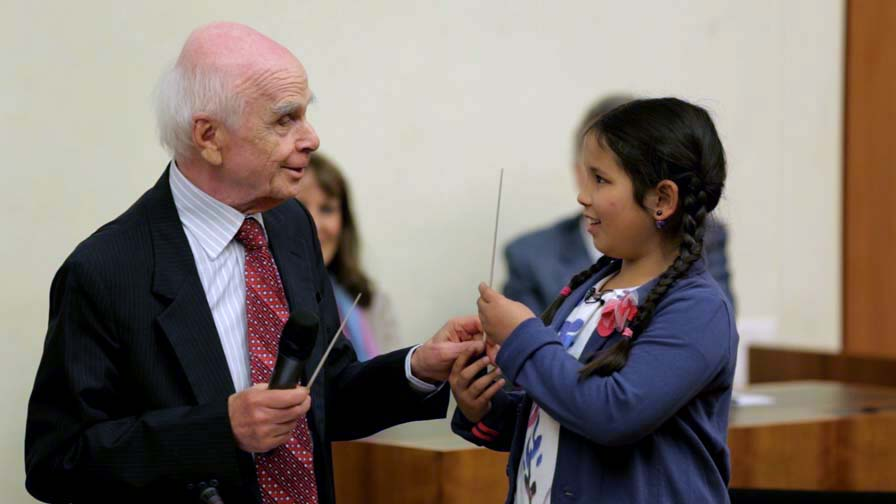 Ervin Laszlo, symbolically handing a 'Conductor's baton' to the younger generations